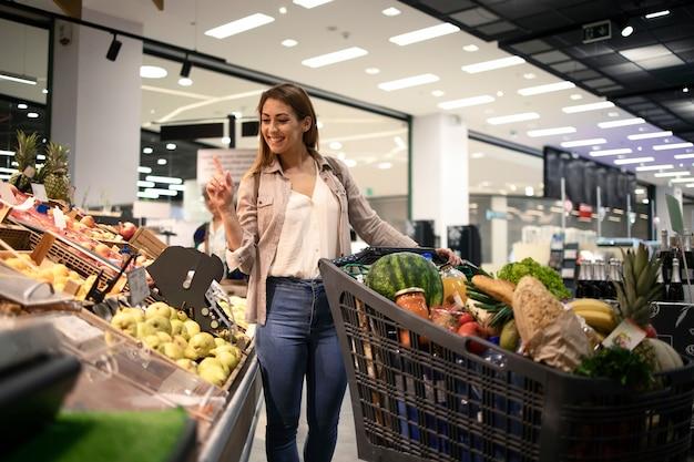 슈퍼마켓에서 구매할 과일을 선택하는 아름 다운 웃는 여자 무료 사진