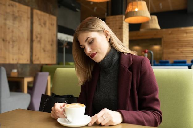 Красивая усмехаясь женщина пьет кофе в кафе. Premium Фотографии