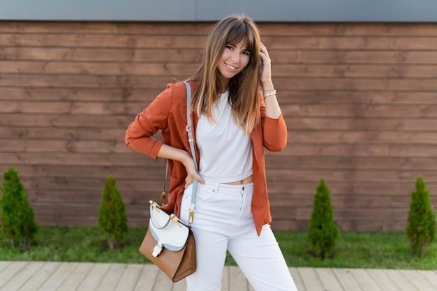 街でポーズのジャケットで笑顔美人。 無料写真
