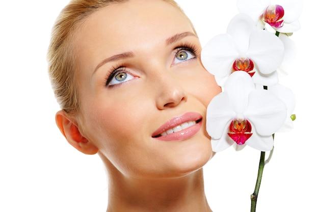 新鮮な白い蘭の花と美しい笑顔の女性の顔 無料写真