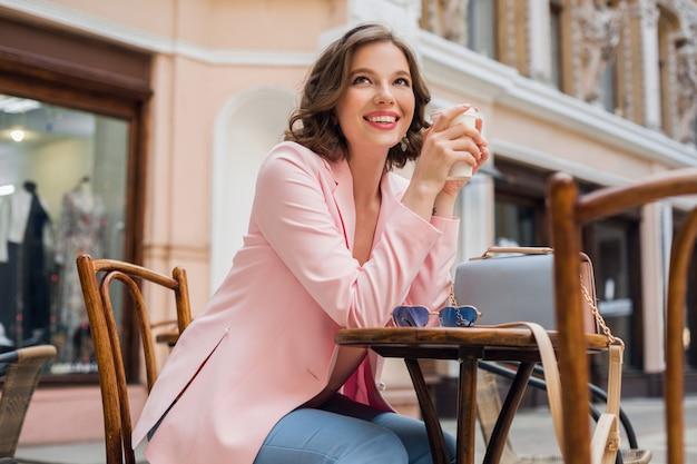 Bella donna sorridente in abito elegante seduto al tavolo che indossa giacca rosa, romantico stato d'animo felice, aspettando il fidanzato a un appuntamento al bar, tendenza moda primavera estate, bere caffè Foto Gratuite
