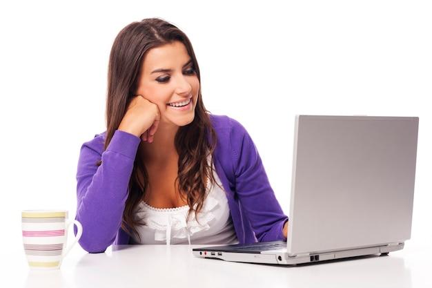 Красивая улыбающаяся женщина с помощью компьютера Бесплатные Фотографии