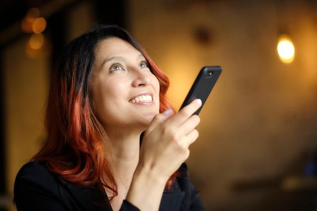 赤い髪の美しい笑顔の女性は彼女の携帯電話を使用しています Premium写真