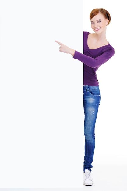 La bella giovane persona femminile sorridente indica il messaggio sul tabellone per le affissioni in bianco Foto Gratuite
