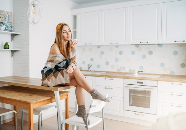 Beautiful smiling young woman fair long hair girl wearing in cozy knitted cardigan with cup of morning cofee sitting on kitchen table at home Premium Photo
