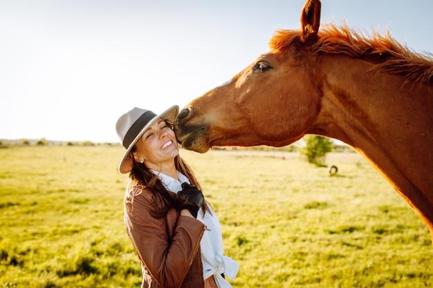 帽子と手袋、夕日のフィールドで茶色の馬で遊んで笑顔の美しい若い女性 Premium写真
