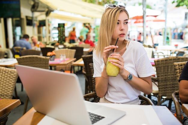 屋外に座っておしゃべり美しい笑顔の若い女性 無料写真