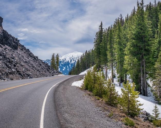 森の隣の美しい雪に覆われた岩だらけの道 無料写真