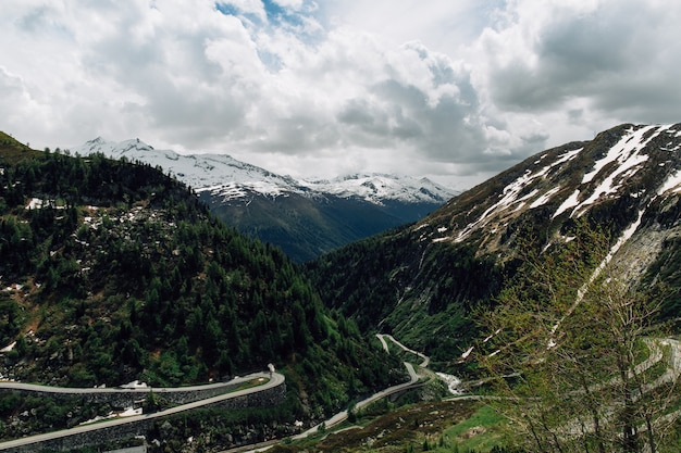 Beautiful snowy swiss alps mountains and curve track in summer time Free Photo