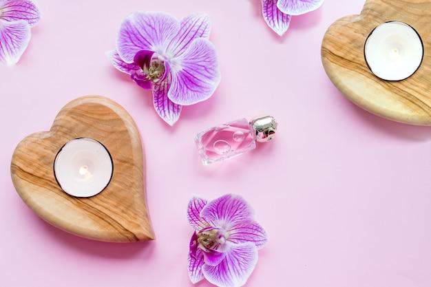 Красивый спа состав. оздоровительный и спа состав с парфюмом, горящими свечами и цветами орхидеи на розовом Premium Фотографии