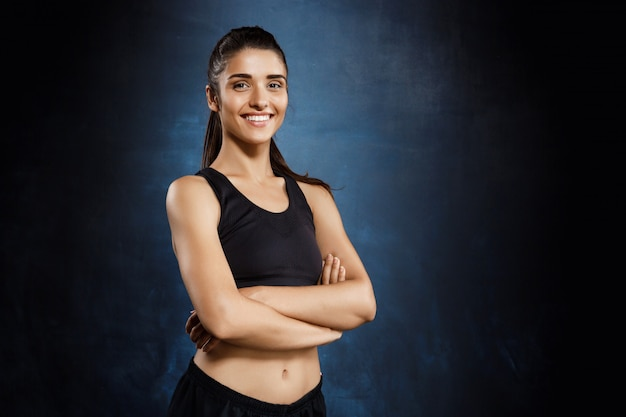 Beautiful sportive girl posing with crossed arms over dark wall. Free Photo