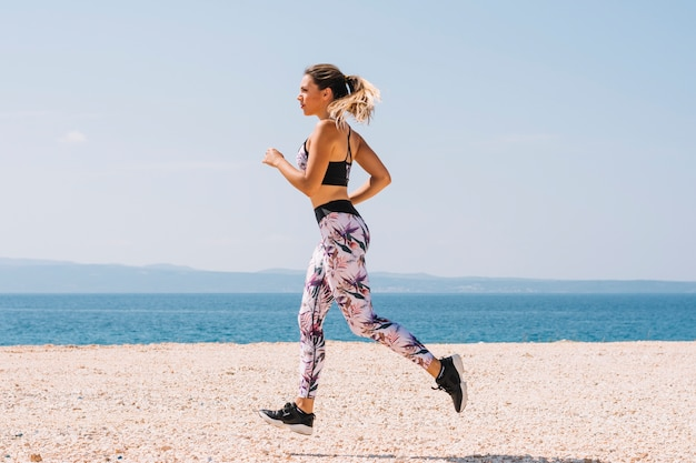Beautiful sportive woman running along beautiful sandy beach Free Photo