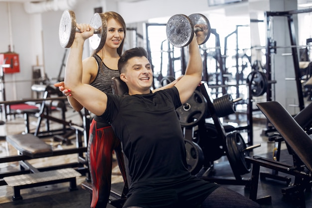 A beautiful sports couple is engaged in a gym Free Photo