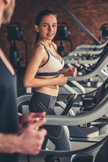 Beautiful sports people are running on a treadmill in gym. Premium Photo