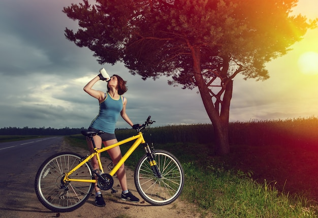Beautiful sports woman with bike drinking water from a bottle. Premium Photo