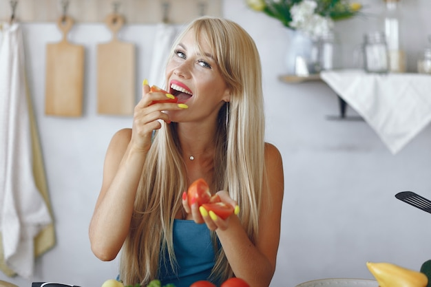 Beautiful and sporty girl in a kitchen with a vegetables Free Photo