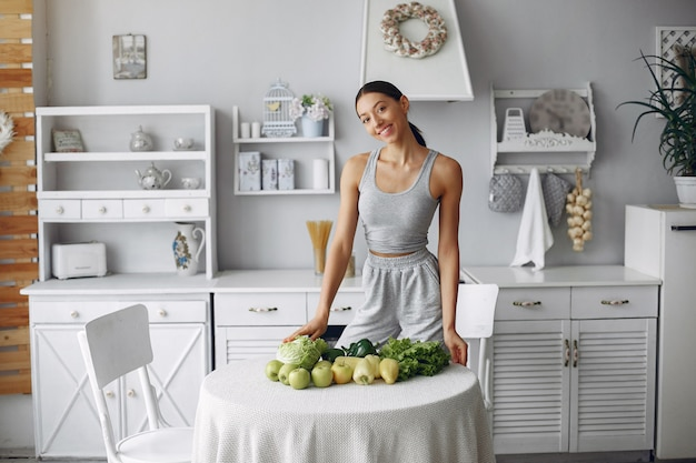 Beautiful and sporty woman in a kitchen with vegetables Free Photo