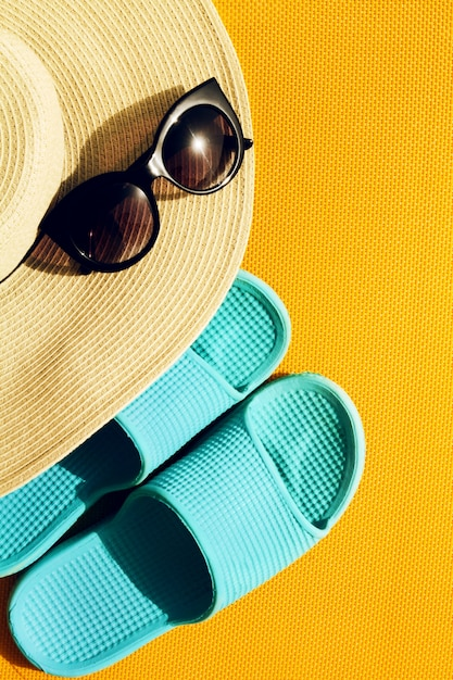 f9425d0027df3 Beautiful straw hat with sunglasses and blue flip flops on yellow ...
