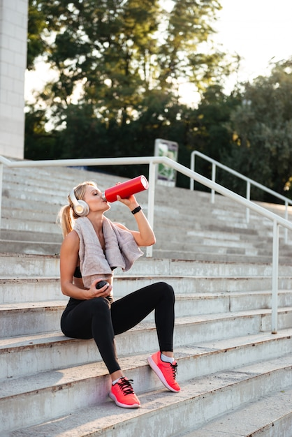 Acqua potabile della bella forte giovane donna di sport Foto Gratuite