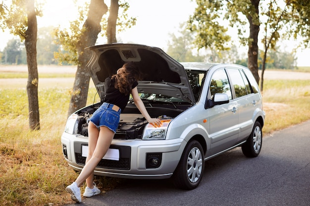 Beautiful student girl wearing mini shorts and black t-shirt leaning on open car hood of a broken down modern car Premium Photo