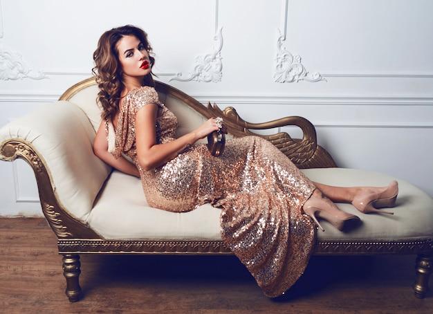 Bella giovane donna sbalorditiva in un fantastico vestito di glitter e paillettes, seduta sul divano di lusso Foto Gratuite