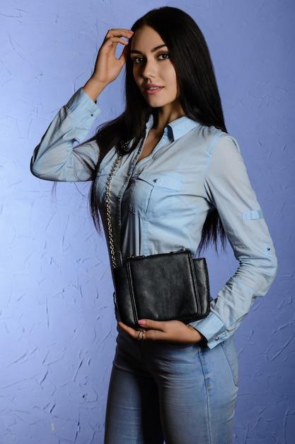 블랙 클러치를 들고 청바지에 아름 다운 세련 된 갈색 머리 프리미엄 사진
