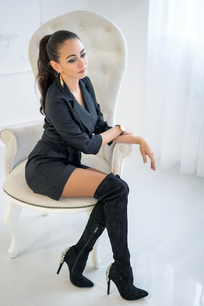 Beautiful stylish confident woman sitting in a white chair in the studio Premium Photo