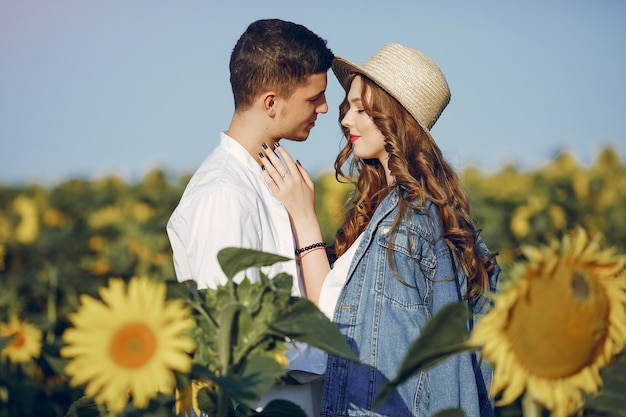 Beautiful and stylish couple in a field with sunflowers Free Photo