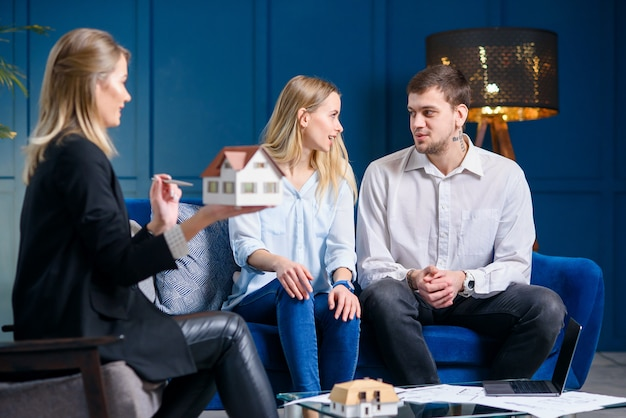 Beautiful stylish family on the meeting with designer, realtor in the stylish blue office. Premium Photo