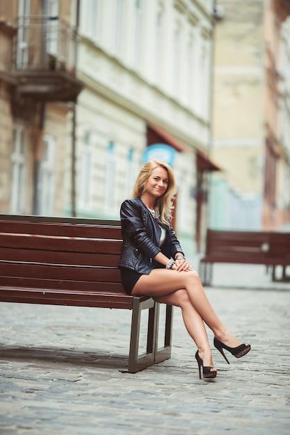 暗い口紅とベンチの上の街で化粧と黒い革のジャケットでスタイリッシュな美少女 Premium写真