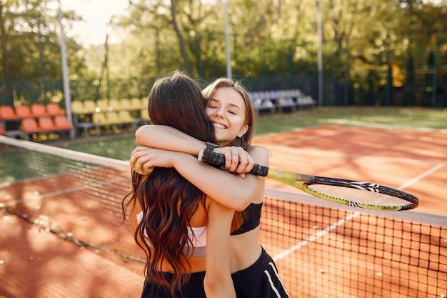 Ragazze belle ed eleganti sul campo da tennis Foto Gratuite