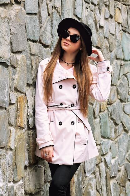 Красивая стильная женщина в пальто и шляпе позирует и касаясь ее волосы Premium Фотографии