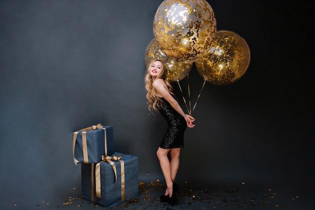 かかとの美しいスタイリッシュな若い女性、長い巻き毛のブロンド、金色のティンセルでいっぱいの大きな風船を持つ黒の高級ドレス。プレゼント、誕生日パーティー、お祝い、笑顔。 無料写真