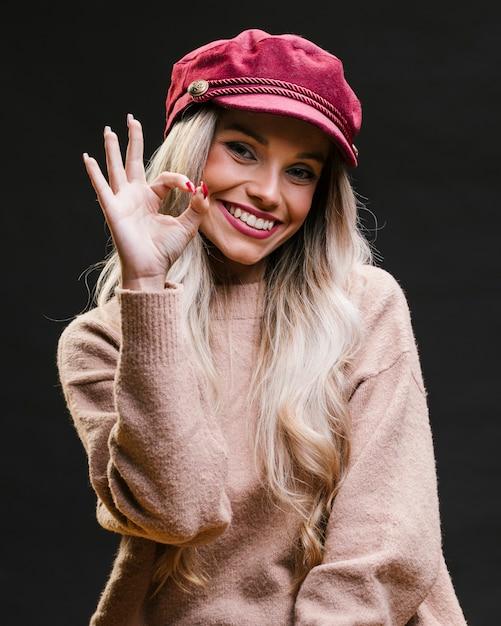 Красивая стильная молодая женщина в розовой кепке, показывая ок жест, стоя на черном фоне Бесплатные Фотографии