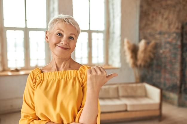 Красивая успешная женщина-агент по недвижимости средних лет со стрижкой пикси, показывает палец вверх, указывая пальцем на уютную гостиную со стильным дизайном интерьера, предлагает квартиру на продажу Бесплатные Фотографии