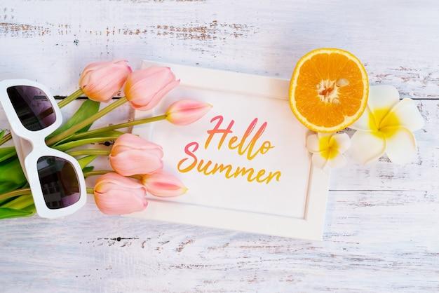 Beautiful summer holiday, beach accessories, orange, sunglasses, flower and photo frame Premium Photo