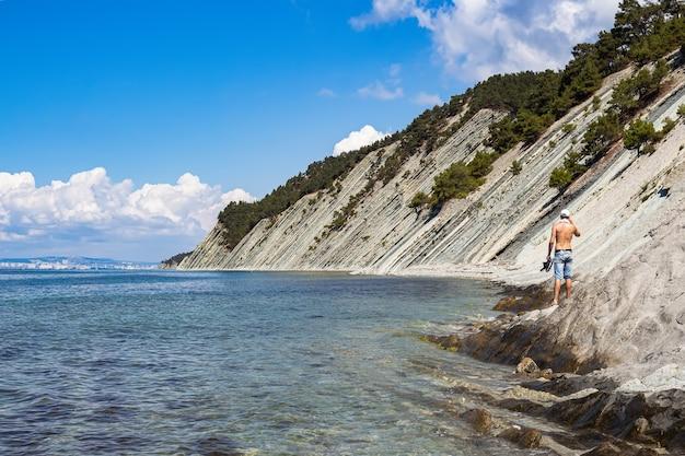 아름 다운 여름 풍경, 구름, 가파른 절벽과 해안에 서있는 남자와 밝은 푸른 하늘. 겔 렌지 크, 러시아, 흑해 연안 프리미엄 사진