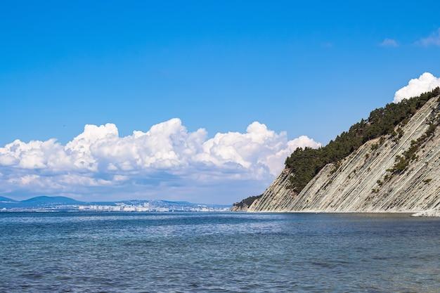 아름다운 여름 풍경, 구름이있는 밝은 푸른 하늘, 나무가있는 가파른 절벽, 야생 돌 해변 및 수평선에 Novorossiysk시의 전망. 러시아, 겔 렌지 크, 흑해 연안 프리미엄 사진