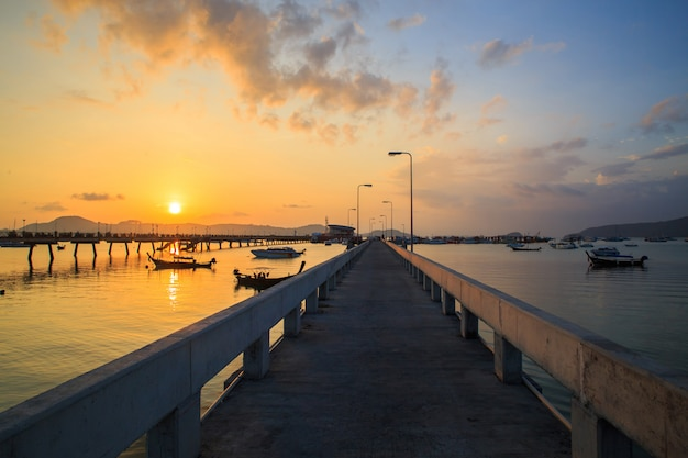 Beautiful sunrise and landscapes of the concrete bridge pier with boats during the sunrise summer travel in phuket Premium Photo