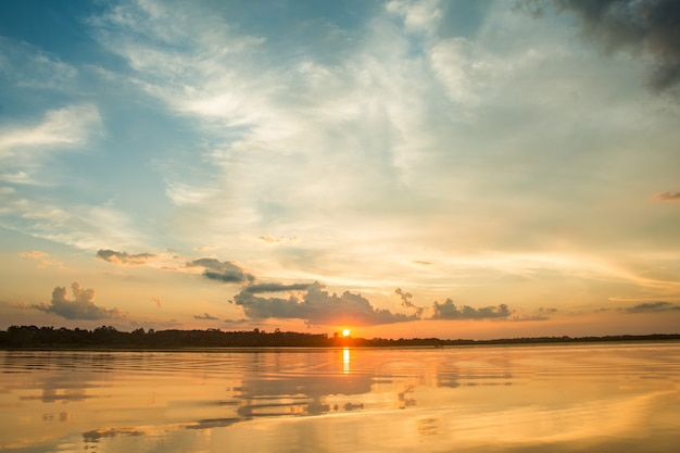 Beautiful sunset behind the clouds above the over lake landscape background. Premium Photo