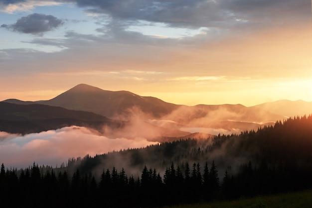 산에서 아름 다운 석양입니다. 오렌지 구름과 안개를 통해 빛나는 태양 빛으로 프리. 무료 사진