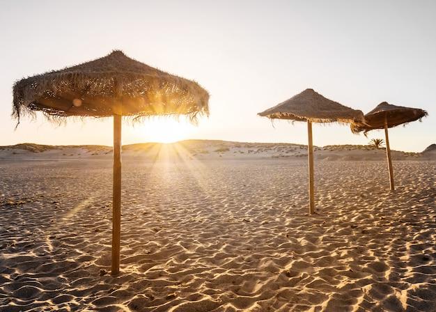 Красивый закат на пляже с зонтиками Бесплатные Фотографии