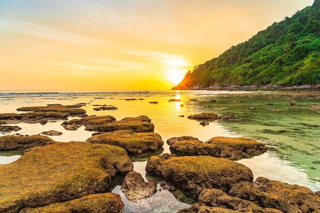 해변 바다 바다와 바위 주위 산 위에 아름다운 일몰 무료 사진