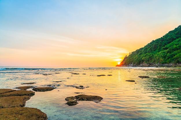 Красивый закат над горой вокруг пляжа, моря, океана и скалы Бесплатные Фотографии