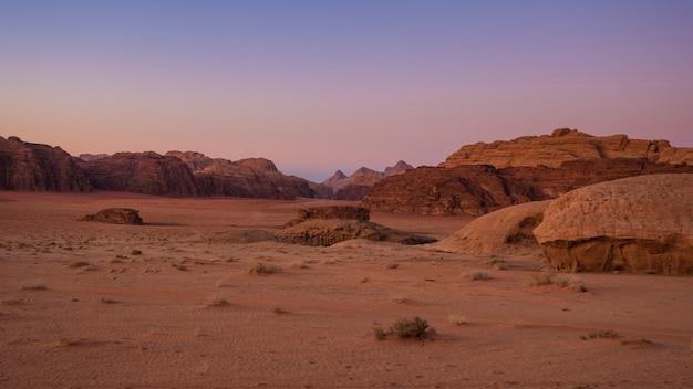 ヨルダンのワディラム砂漠の山々を見下ろす美しい夕日 Premium写真