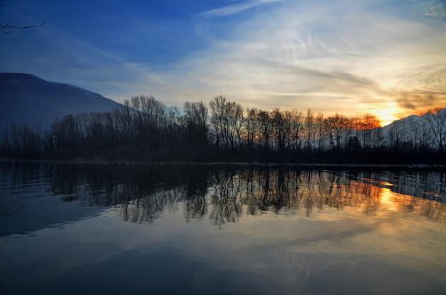 水に映る木のシルエットと湖の美しい夕日の風景 無料写真