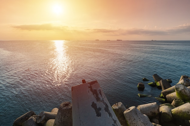 Beautiful sunset seascape. travel dreams and motivation. breakwaters tetrapods on shore of pier. cargo ships on the horizon. Premium Photo
