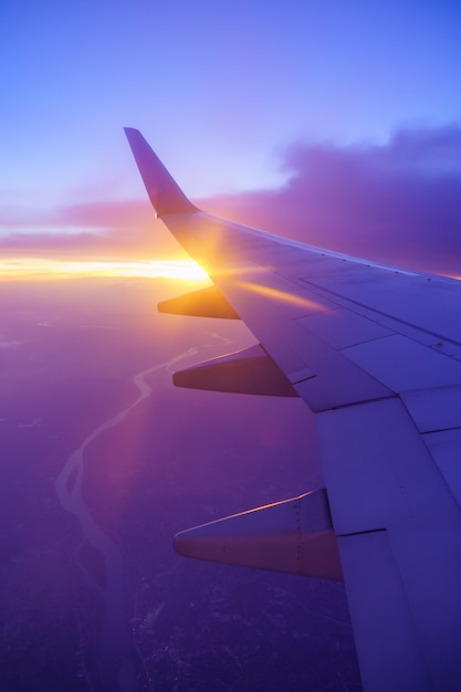 Beautiful sunset, sky on the top view, airplane flying view from inside window and cloud Premium Photo
