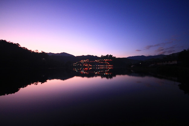 Beautiful sunset and twiligth of sky reflection on water surface and lake at  hill tribe village in thailand Premium Photo