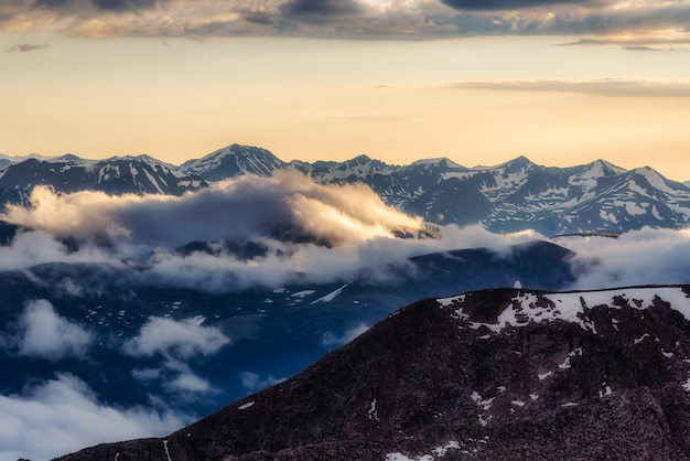 Beautiful sunset view with snow covered mountains and clouds as viewed from mount evans in colorado Free Photo